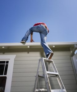 Man climbing onto roof from ladder