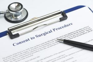 Surgical consent form on clipboard with pen and stethoscope adjacent